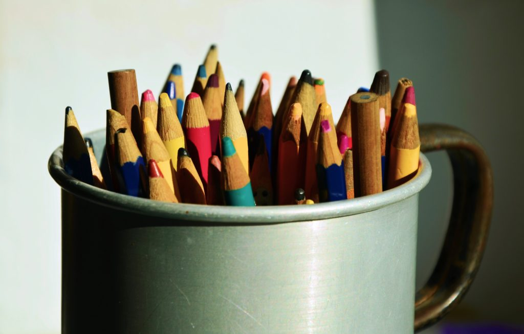 A metal cup full of color pencils.