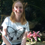 Mel is smiling in a white T-shirt with a large butterfly graphic and holding her cane.