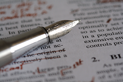 A silver fountain pen rests across two columns of text marked up with red ink.
