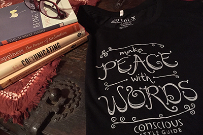 "Meditation books, glasses, and a T-shirt with a ""Make Peace With Words"" hand-lettered design on a wooden trunk."