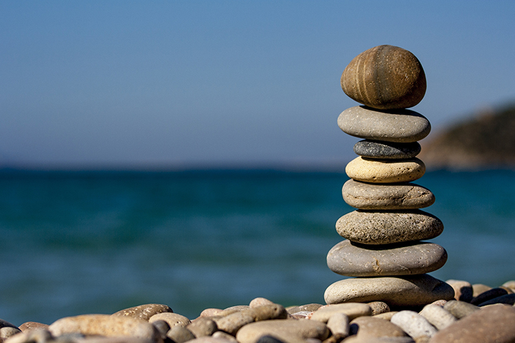 A stack of eight stones with the blue sky and ocean out of focus in the background.