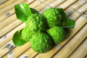 A cluster of bright-green makrut limes on a bamboo surface.