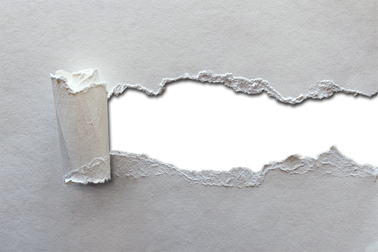 A piece of gray paper has a strip torn from its center to reveal the whiteness beneath.