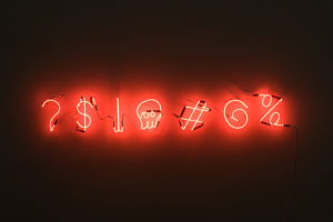 Lit against a black background are red neon symbols for question mark, dollar sign, spear-like object, skull, hashtag, swirl, and percent sign.