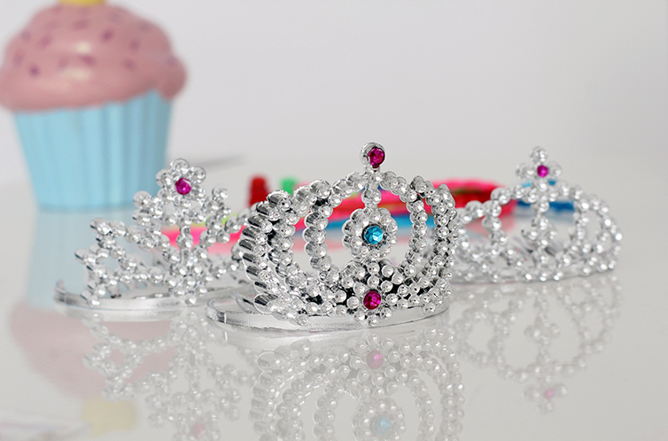 Toy tiaras, a plastic cupcake, and other party favors on a glossy white surface.