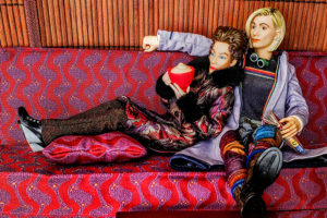 Action figures of Missy and the Thirteenth Doctor sit cozily on a couch.