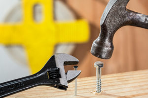 The jaws of an adjustable wrench hover around the head of a nail, while a hammer hovers over a bolt, both tools unable to complete the task.