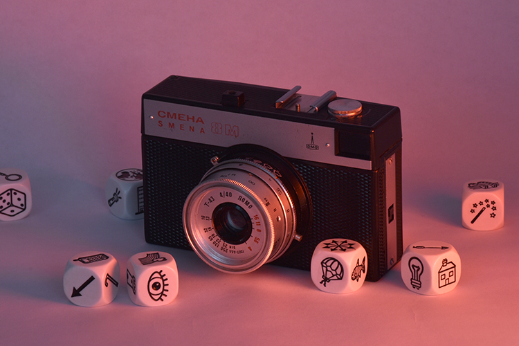 Boxy point-and-shoot camera surrounded by six-sided dice with icons of random objects, like an eye, arrow, cell phone, hot air balloon, fish, light bulb, wand, house, magnifying glass, and die.