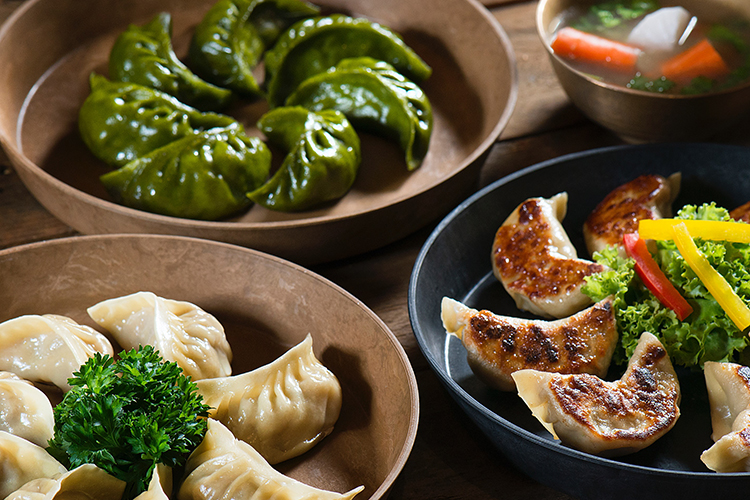 Three varieties of Korean dumplings beautifully plated with garnish.